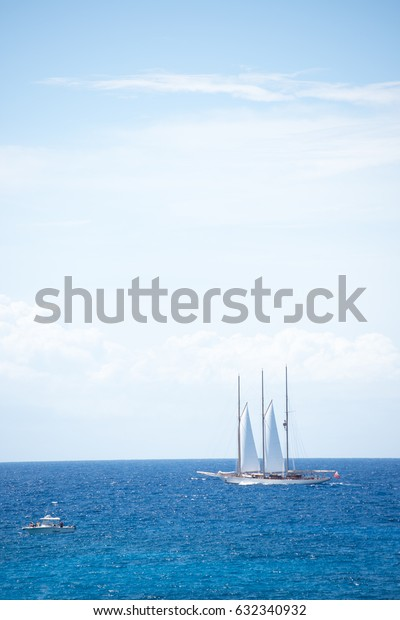 White Large Yacht in Beautiful Turquoise Water of Caribbean Sea and Blue Sky with Clouds
