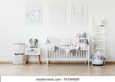 White laundry bag with painted eyelashes standing next to a nightstand with a stuffed animal elephant sitting on it in a children room interior