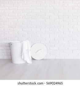White laundry basket standing in spacious room with light flooring and brick wall