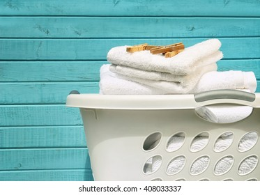 White laundry basket with towels and clothes pins