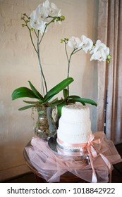 White layered decorated wedding cake and flowers on table in reception hall