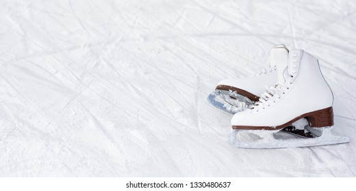 white leather figure skates and copy space over ice background with marks from skating