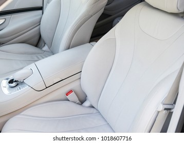 White leather interior of the luxury modern car. Leather comfortable white seats and multimedia. Steering wheel and dashboard. automatic gear stick. Car interior details