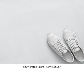White leather sneakers on white background. Pair of fashion trendy white sport shoes or sneakers with copy space for text or design. Overhead shot of new white sneakers,monochrome.Top view or flat lay