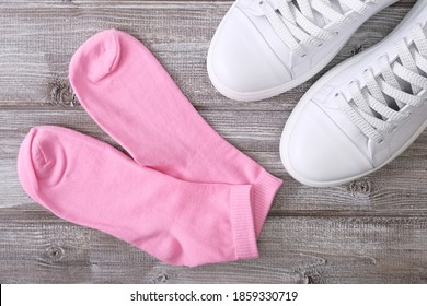 White leather sneakers and pink cotton socks on wooden background, a set for walking and workout.