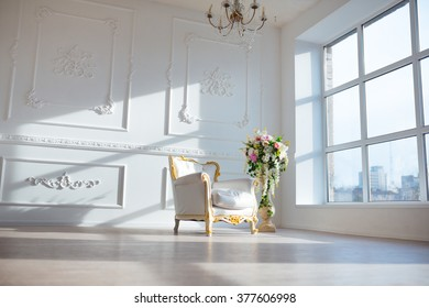 White leather vintage style chair in classical interior room with big window and spring flowers