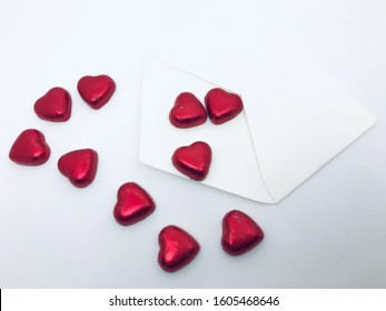 A white letter envelope with  heart-shaped chocolate candies, isolated on white background, love, romance, Valentines' Day concept.