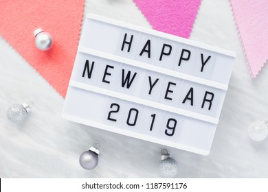 White Letter Lightbox with Happy New Year 2019 and silver ornaments with pink flag on luxury marble background, light banner Flat lay luxury holiday celebration still life.