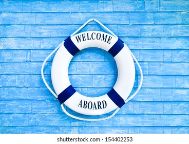 White Life buoyancy with welcome aboard on blue wall