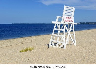 White Lifeguard chair on sand beach with blue sky, no people