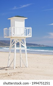 White lifeguard tower on a deserted beach on a clear sunny day