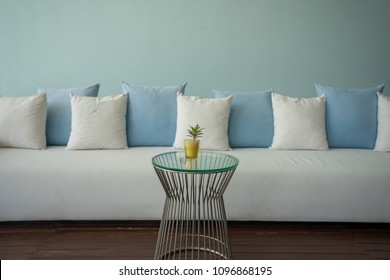 White and light blue pillows on long white sofa decorated in minimal style.