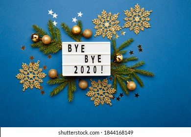 White light box with text Bye Bye 2020, fir branches , golden christmas balls, snowflakes and stars on blue background. Flat lay, top view, copy space. Christmas frame, New year banner mockup