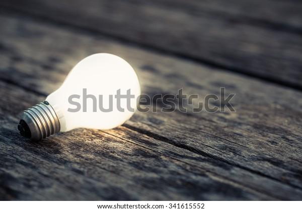 木の地面に輝く白い電球