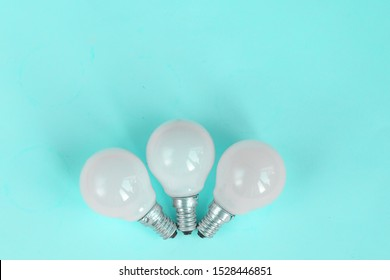 White light bulb isolated on mint green color background with space for text