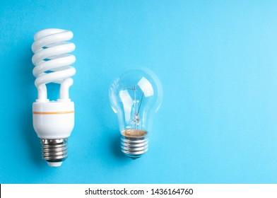 White light bulb on blue background. Economical light bulb. Neon light.