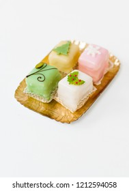 White, light pink, yellow and green petits fours, small cake squares decorated with fondant, chocolate, sugar icing and marzipan Christmas ornaments