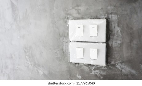 White light switch on concrete wall. Closeup of a lighting switch on concrete wallpaper background with copy space.