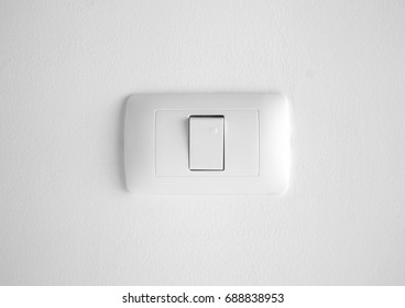 White light switch on concrete wall.