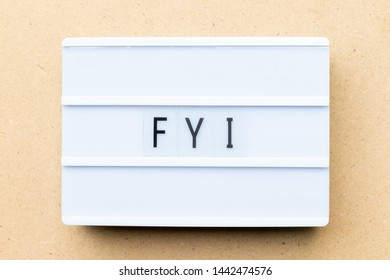 White lightbox with word FYI (Abbreviation of For your information) on wood background