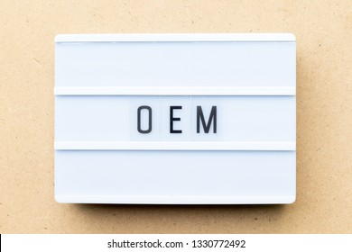 White lightbox with word OEM (Abbbreviation of Original Equipment Manufacturer) on wood background
