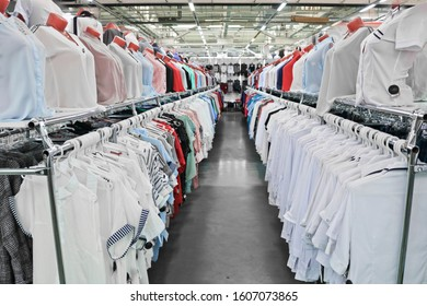 White and light-colored women's shirts hang on hangers and mannequins in a clothing and shoe store.