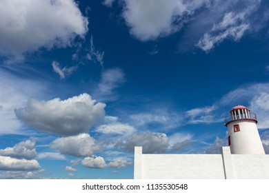 White lighthouse against the blue sky with beautiful clouds.
