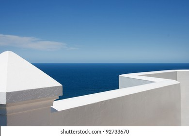 White lighthouse fence overlooking blue sea and sky