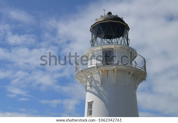 white lighthouse in front of blue sky and some clouds