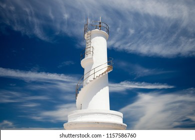 White lighthouse and intense blue sky with clouds
