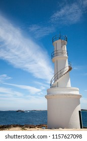 White lighthouse and intense blue sky with clouds and in the background a yacht sails across the sea.