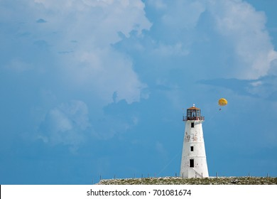 White Lighthouse on a cliff with people parasailing in the background