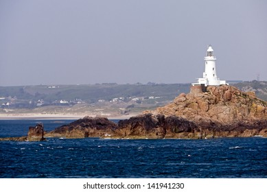 White lighthouse; white lighthouse on jagged rocky outcrop in deep blue sea; shore-line visible in distance; good copy-space over pale blue sky