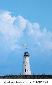 White Lighthouse with people parasailing in the background