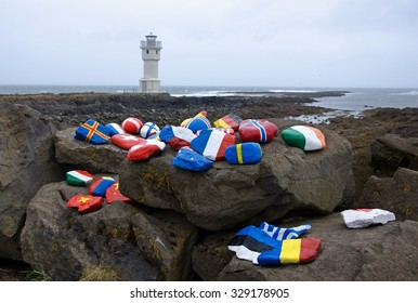 White lighthouse at the port of Akranes with national flags painted on rock, Iceland