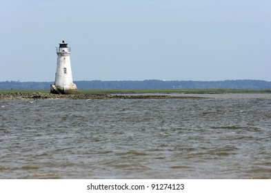 White lighthouse with water in the foreground in Savannah, Georgia
