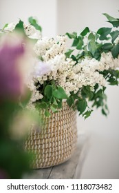 White Lilac Stands in a Wicker Basket by the Window