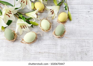 White lilies and easter eggs on wooden background, copy space.
