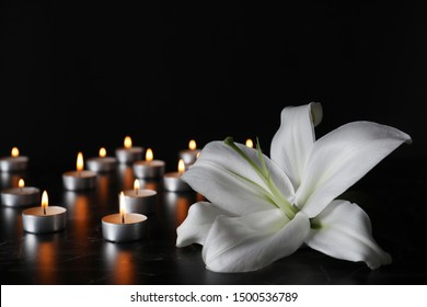 White lily and blurred burning candles on table in darkness, closeup with space for text. Funeral symbol