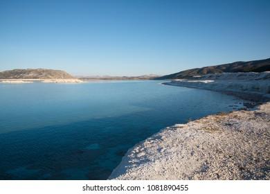 white limestone on shore of beautiful calm lake, salda golu, turkey