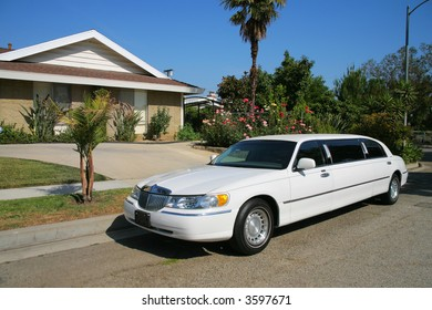 White limousine next to a residential house.
