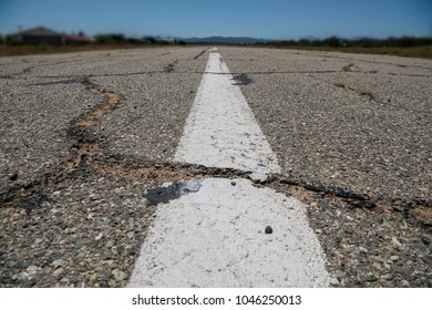 White line on cracked pavement from low perspective leading towards mountain range