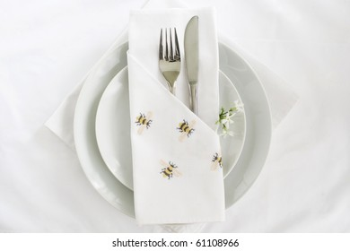 White linen place setting with knife and fork and embroidered bee napkin