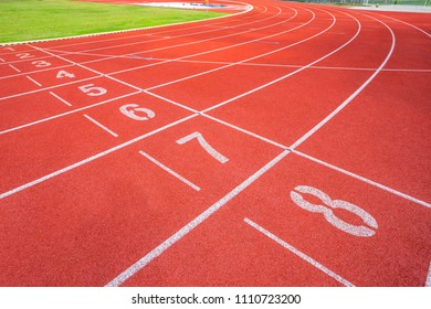 White lines of stadium and texture of running racetrack red rubber racetracks in outdoor stadium are 8 track and green grass field,empty athletics stadium with track,football field, soccer field.
