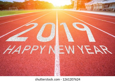 White lines of stadium and texture of running racetrack red rubber racetracks with 2019 Happy New Year text.