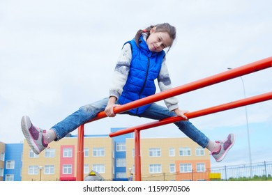 White little girl wearing blue jeans and sleeveless jacket on gymnastic bars on a sports ground outdoor