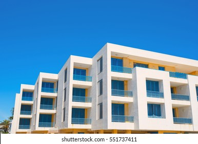 White living house with appartments and balconies in blue color.
