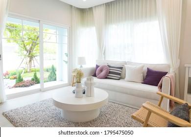 weißes Wohnzimmer mit rundem Tisch und violettem Kissen am großen Fenster.