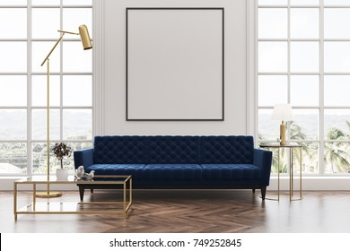 White living room interior with a wooden floor, loft windows, a blue sofa, a coffee table and a framed vertical poster on a white wall. 3d rendering mock up