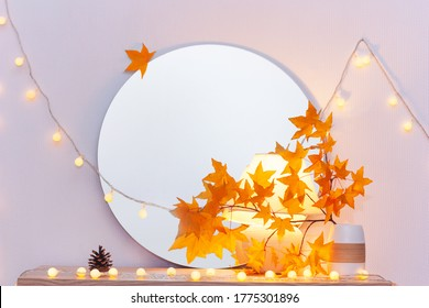 White living room minimalist interior shelf mockup. Autumn decoration room home interior. Light garland yellow red maple leaves lamp mirror. Modern empty wall. Copy space selective focus banner design